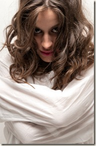 Young insane woman with straitjacket looking at camera close-up portrait